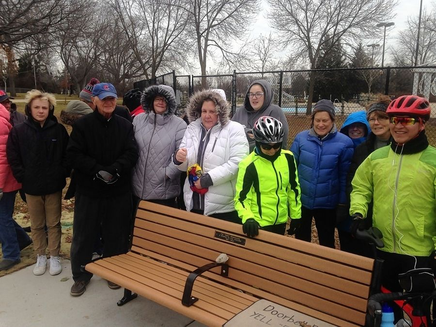 Members of local bike clubs gather around the park bench they dedicated in Frontier Park in Arlington Heights in honor of longtime biking enthusiast Jim Shoemaker. His daughter, Carrie, is in the white parka.