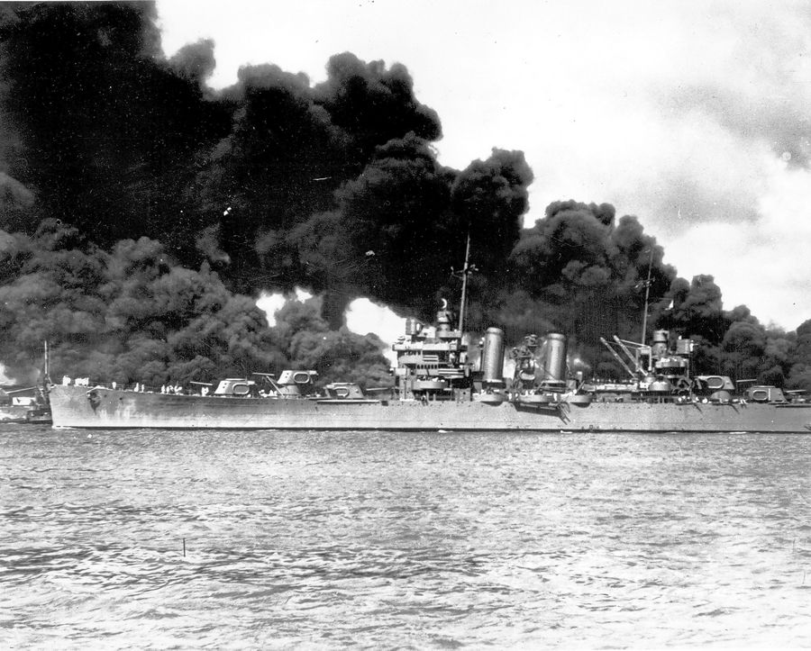 An undamaged light cruiser steams out past the burning USS Arizona and takes to sea with the rest of the fleet during the Japanese aerial attack on Pearl Harbor, Hawaii, on Dec. 7, 1941.