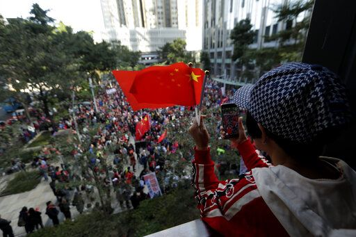Pro-Beijing supporters wave the Chinese national flags during a rally in Hong Kong on Saturday, Dec. 7, 2019. Six months of unrest have tipped Hong Kong's already weak economy into recession.