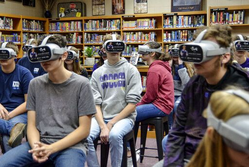 "Freshman English students at Sullivan High School use VR headsets to learn about Eva Kor's life and legacy as a part of the ""Virtual Reality: An Eva Experience"" on Monday, Nov. 25, 2019, at the school in Sullivan, Ind. (Austen Leake/Tribune-Star via AP)"