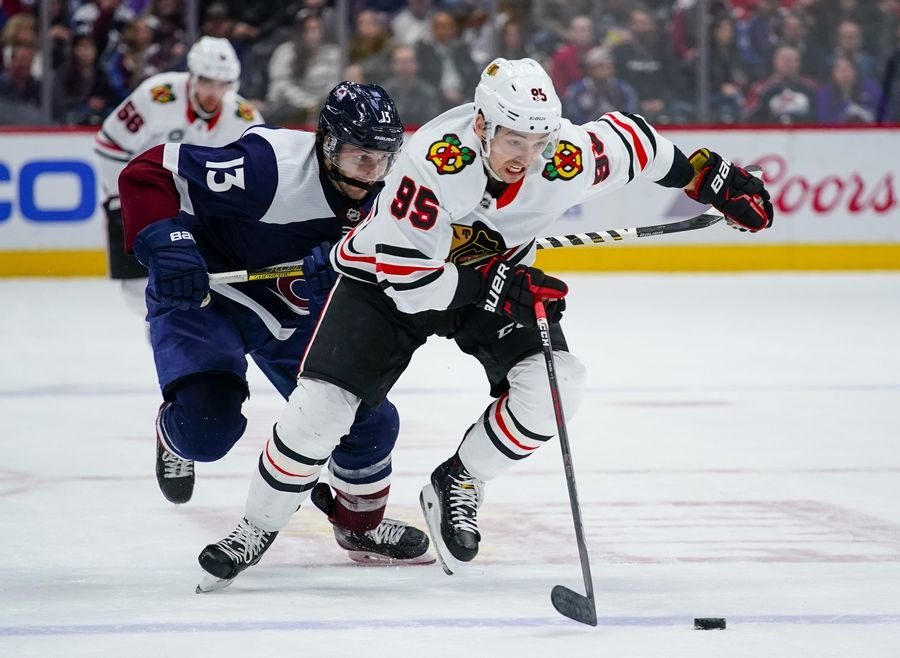 Chicago Blackhawks right wing Dylan Sikura (95) moves the puck against Colorado Avalanche center Alexander Kerfoot (13) during the first period of an NHL hockey game, Saturday, March 23, 2019 in Denver.