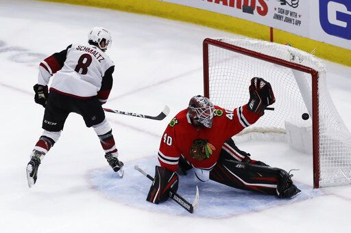 Arizona Coyotes center Nick Schmaltz, left, scores against Chicago Blackhawks goalie Robin Lehner in a shootout of an NHL hockey game Sunday, Dec. 8, 2019, in Chicago. The Coyotes defeated the Blackhawks 4-3.