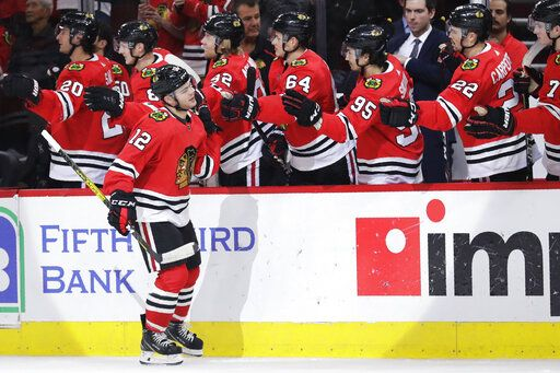 Chicago Blackhawks left wing Alex DeBrincat (12) celebrates with teammates after scoring a goal during the first period of an NHL hockey game against the Arizona Coyotes, Sunday, Dec. 8, 2019, in Chicago.