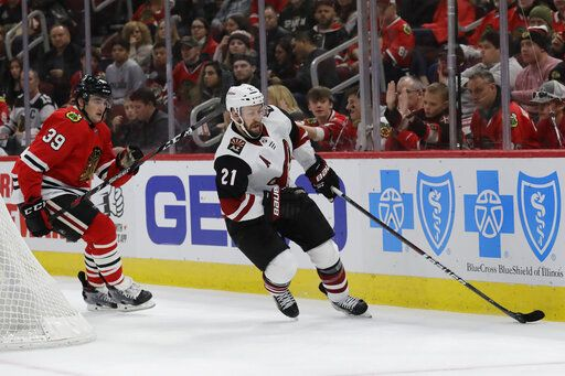 Arizona Coyotes center Derek Stepan, right, controls the puck past Chicago Blackhawks defenseman Dennis Gilbert during the first period of an NHL hockey game Sunday, Dec. 8, 2019, in Chicago.