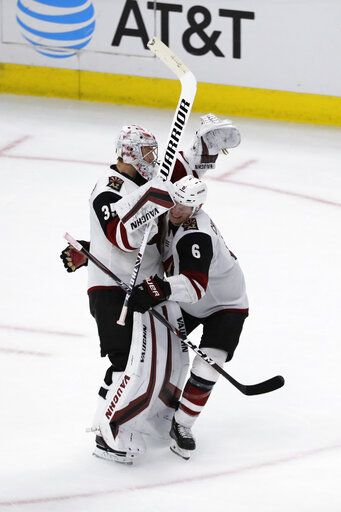 Arizona Coyotes goalie Darcy Kuemper, left, celebrates with defenseman Jakob Chychrun after the Coyotes defeated the Chicago Blackhawks 4-3 in a shootout of an NHL hockey game Sunday, Dec. 8, 2019, in Chicago.