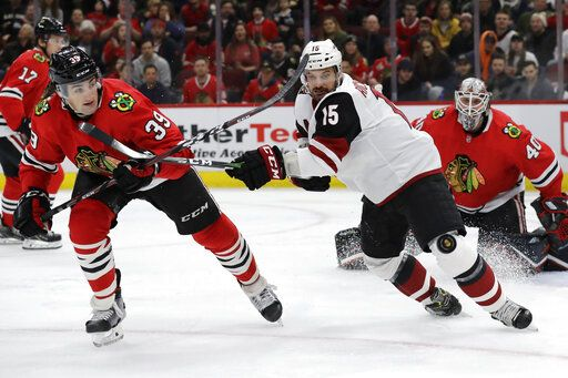 Arizona Coyotes center Brad Richardson, right, and Chicago Blackhawks defenseman Dennis Gilbert chase as they battle for the puck during the first period of an NHL hockey game Sunday, Dec. 8, 2019, in Chicago.