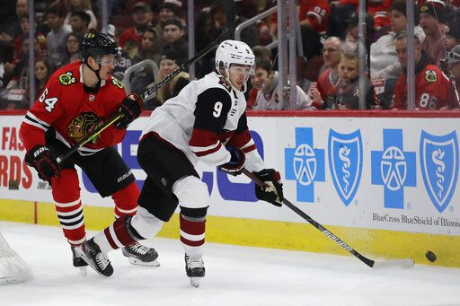 Arizona Coyotes right wing Clayton Keller, right, looks to pass against Chicago Blackhawks center David Kampf during the first period of an NHL hockey game Sunday, Dec. 8, 2019, in Chicago.