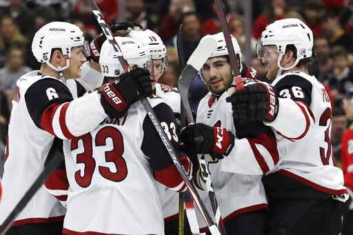 Arizona Coyotes right wing Christian Fischer, right, celebrates with teammates after scoring his goal against the Chicago Blackhawks during the first period of an NHL hockey game Sunday, Dec. 8, 2019, in Chicago.