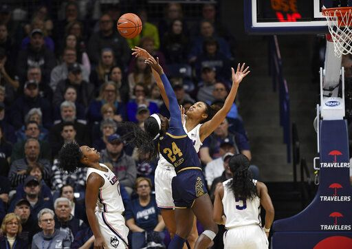Connecticut's Olivia Nelson-Ododa blocks a shot attempt from Notre Dame's Destinee Walker, left, as Connecticut's Christyn Williams, far left, and Crystal Dangerfield, right, defend in the first half of an NCAA college basketball game, Sunday, Dec. 8, 2019, in Storrs, Conn.