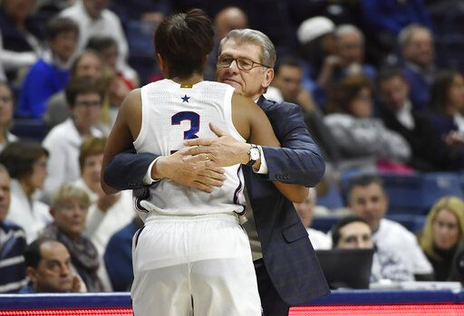 Connecticut head coach Geno Auriemma hugs Connecticut's Megan Walker in the second half of an NCAA college basketball game, Sunday, Dec. 8, 2019, in Storrs, Conn.