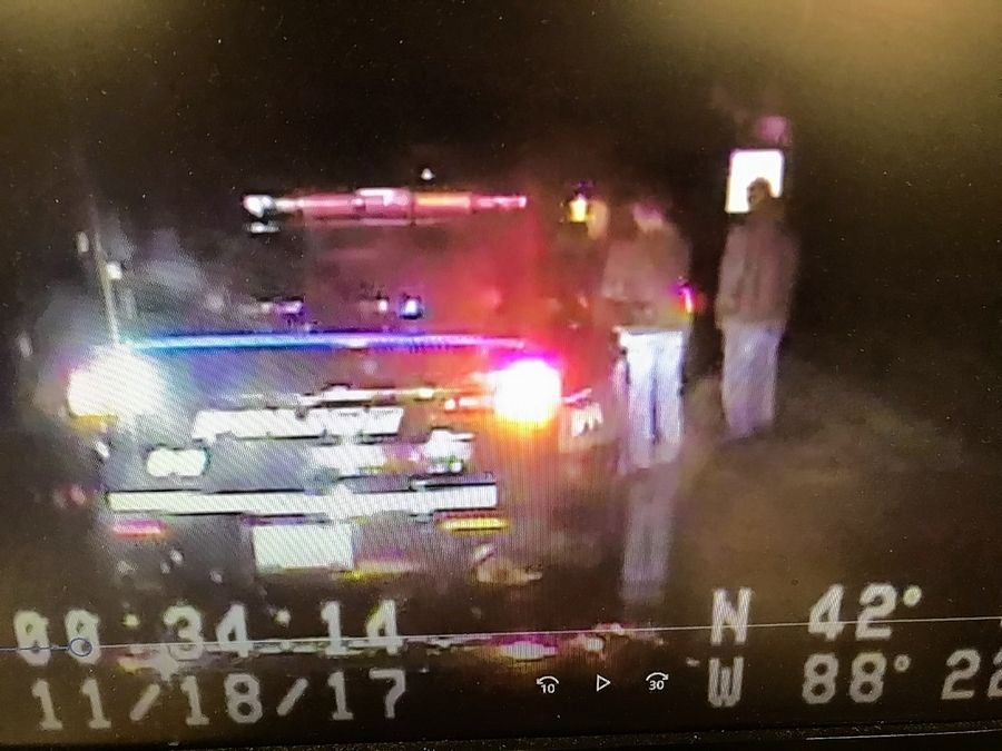 This image shows two men standing on the side of the road next to a police officer after a traffic stop Nov. 18, 2017, in Gilberts. The 17-minute stop involved a car that documents showed was registered to South Elgin police officer Shane Christenson.