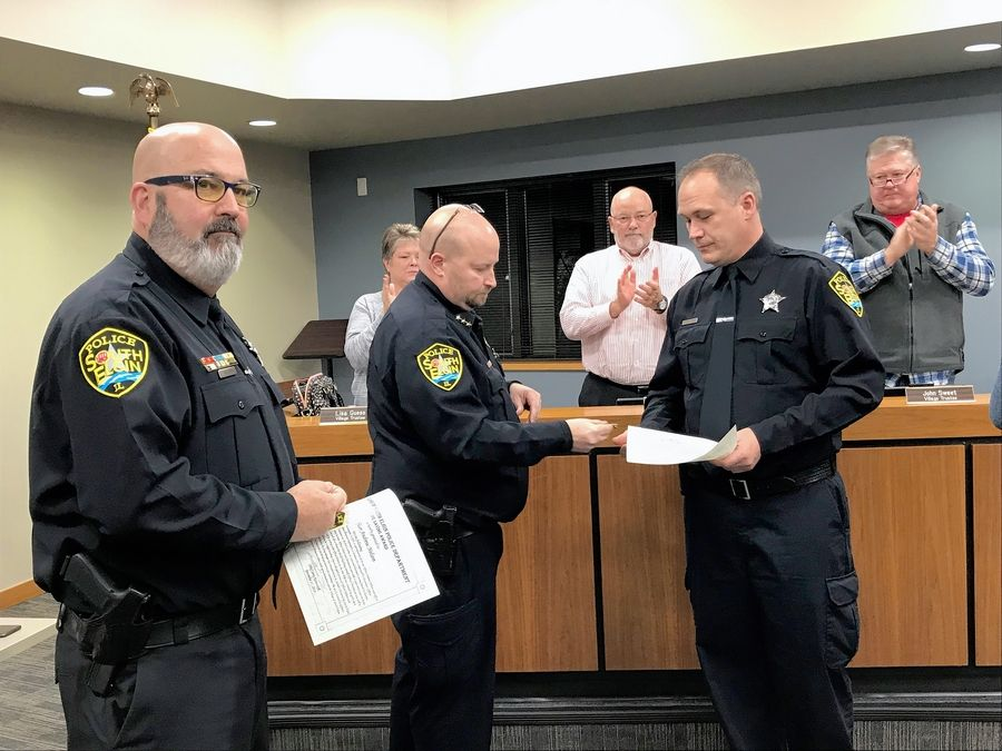 "South Elgin police officer Shane Christenson, right, along with officer Andrew Nelson, left, was honored by Police Chief Jerry Krawczyk and the village board in December 2018 after the officers saved a resident's life. Christenson is working under a ""last chance"" disciplinary agreement."