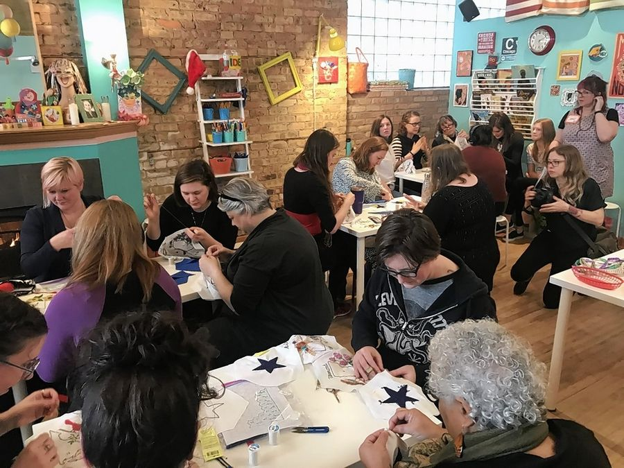 In a collaboration with hundreds of other volunteers, three dozen women sew together patches for a quilt at Wishcraft Workshop in Chicago. Organizer Shannon Downey bought the plan at a Mount Prospect estate sale and is using it to bring people together.