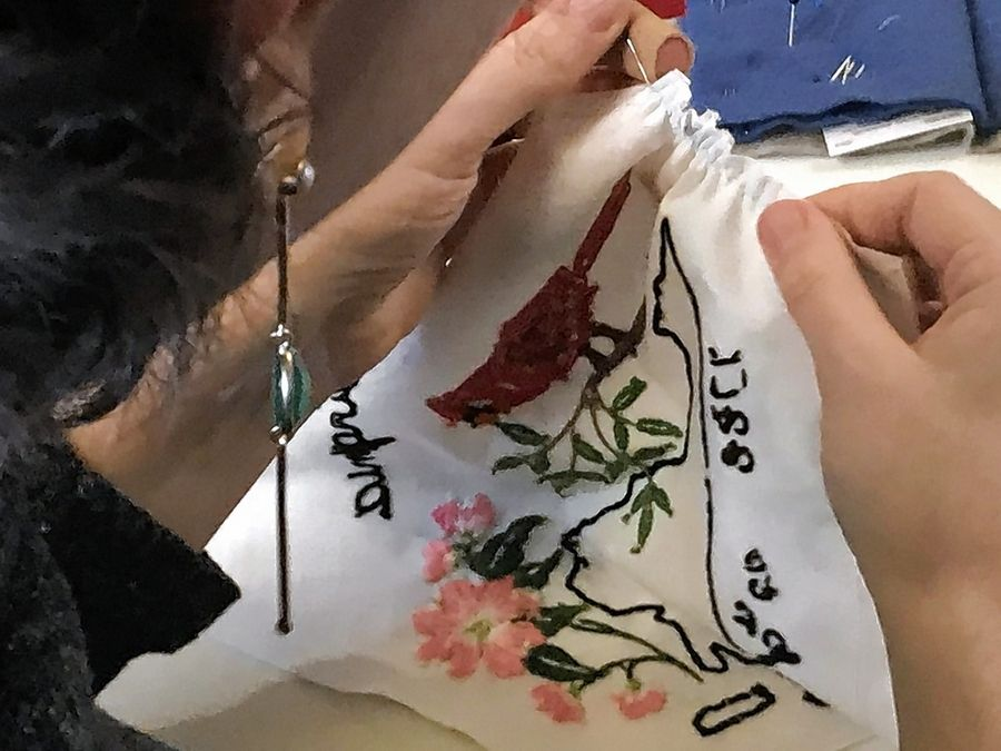 Working with a patch mailed in from an embroiderer in another state, a volunteer sews it as part of constructing a massive quilt featuring a map of the United States.