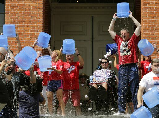 FILE - In this Monday, Aug. 10, 2015 file photo, Massachusetts Gov. Charlie Baker, right center, and Lt. Gov. Karyn Polito, third from left, participate in the Ice Bucket Challenge with the man who inspired the event, Pete Frates, seated in center, to raise money for ALS research, at the Statehouse in Boston. Frates, who was stricken with amyotrophic lateral sclerosis, or ALS, died Monday, Dec. 9, 2019. He was 34.