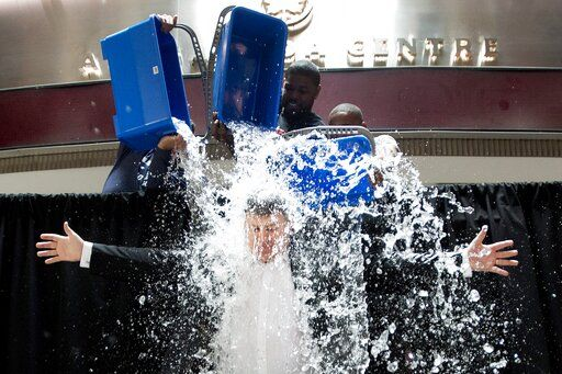 FILE - In this Aug. 20, 2014, file photo, Tim Leiweke, President and CEO of Maple Leaf Sports Entertainment, participates in the ALS Ice Bucket Challenge as Nazem Kadri, rear left, of the Toronto Maple Leafs, Amir Johnson, center, of the Toronto Raptors and Jermain Defoe, right, of Toronto FC dump ice water on him in Toronto. Pete Frates, who was stricken with amyotrophic lateral sclerosis, or ALS, and inspired the Ice Bucket Challege, died Monday, Dec. 9, 2019. He was 34. (Nathan Denette/The Canadian Press via AP, File)