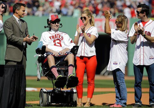 FILE - In this April 13, 2015, file photo, Pete Frates, former Boston College baseball player whose Ice Bucket Challenge raised millions for ALS research, is applauded by Boston Red Sox general manager Ben Cherington, far left, and his wife Julie Frates, center, along with other family members prior to the home opener baseball game between the Boston Red Sox and the Washington Nationals at Fenway Park in Boston. Frates, who was stricken with amyotrophic lateral sclerosis, or ALS, died Monday, Dec. 9, 2019. He was 34.