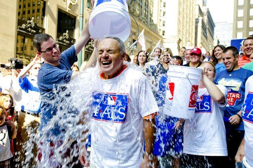 FILE - In this Aug. 20, 2014 file photo, Major League Baseball Commissioner-elect Rob Manfred participates in the ALS Ice-Bucket Challenge outside the organization's headquarters in New York. Pete Frates, who was stricken with amyotrophic lateral sclerosis, or ALS, and inspired the Ice Bucket Challege, died Monday, Dec. 9, 2019. He was 34.