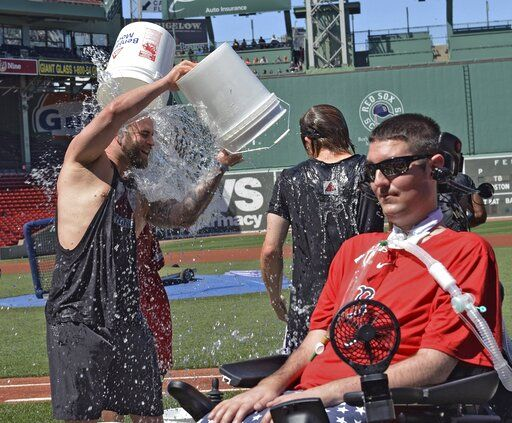 FILE - In this July 31, 2015, file photo, Boston Red Sox player Mike Napoli takes part in the re-launch of the Ice Bucket Challenge as former Boston College baseball player Pete Frates, right, looks on at Fenway Park in Boston. Frates, whose determined battle with Lou Gehrig's disease helped inspire the ALS ice bucket challenge that has raised more than $200 million worldwide, died Monday, Dec. 9, 2019. He was 34.  (Arthur Pollock/The Boston Herald via AP, File)