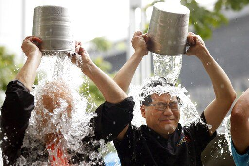 FILE - In this Aug. 20, 2014 file photo, Hong Kong Secretary for Commerce and Economic Development Gregory So, right, and Hong Kong businessman Allan Zeman take part in the Ice Bucket Challenge fund raising event in Hong Kong. Pete Frates, who was stricken with amyotrophic lateral sclerosis, or ALS, and inspired the Ice Bucket Challege, died Monday, Dec. 9, 2019. He was 34.