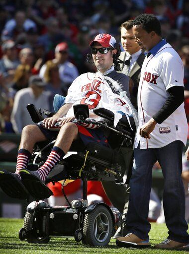 FILE - In this April 13, 2015, file photo, Pete Frates, center, former Boston College baseball player whose Ice Bucket Challenge raised millions for ALS research, is escorted by Boston Red Sox general manager Ben Cherington, second from right, and Pedro Martinez, special assistant to the general manager, right, during ceremonies prior to the home opener baseball game between the Red Sox and the Washington Nationals, in Boston. Frates, who was stricken with amyotrophic lateral sclerosis, or ALS, died Monday, Dec. 9, 2019. He was 34.