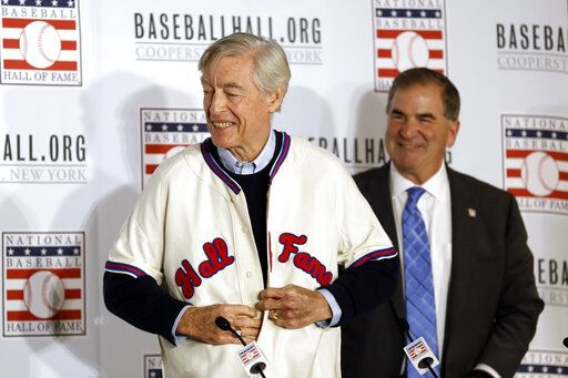 Former St. Louis Cardinals catcher Ted Simmons buttons a Hall of Fame jersey as National Baseball Hall of Fame President Tim Mead looks on, right, during the Major League Baseball winter meetings Monday, Dec. 9, 2019, in San Diego. Simmons was elected into the Hall of Fame Sunday.