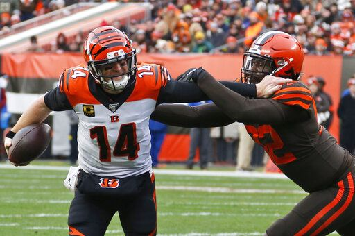 Cincinnati Bengals quarterback Andy Dalton (14) scrambles past Cleveland Browns defensive end Chad Thomas (92) during the second half of an NFL football game, Sunday, Dec. 8, 2019, in Cleveland.