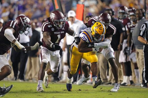 LSU running back Clyde Edwards-Helaire (22) carries against Texas A&M linebacker Buddy Johnson (1) and defensive back Keldrick Carper during the second half of an NCAA college football game in Baton Rouge, La., Saturday, Nov. 30, 2019. LSU won 50-7.