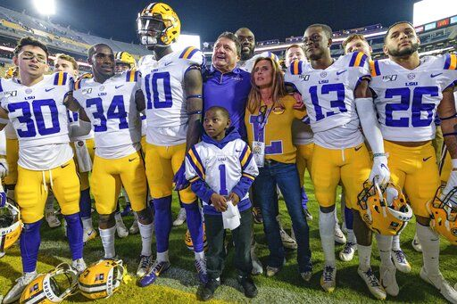LSU coach Ed Orgeron; his wife, Kelly; and players celebrate the team's 56-20 victory over Arkansas in an NCAA college football game in Baton Rouge, La., Saturday, Nov. 23, 2019.