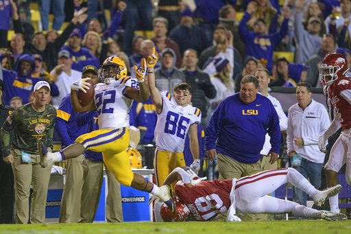 LSU running back Clyde Edwards-Helaire (22) gets away from Arkansas defensive back Myles Mason (18) on a touchdown run during the second half of an NCAA college football game in Baton Rouge, La., Saturday, Nov. 23, 2019.