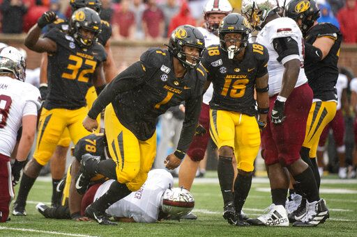 FILE - In this Oct. 5, 2019, file photo, Missouri defensive lineman Jordan Elliott, center, celebrates after tackling Troy quarterback Kaleb Barker, bottom, during the first half of an NCAA college football game, in Columbia, Mo. Elliott was selected to The Associated Press All-Southeastern Conference football team, Monday, Dec. 9, 2019.