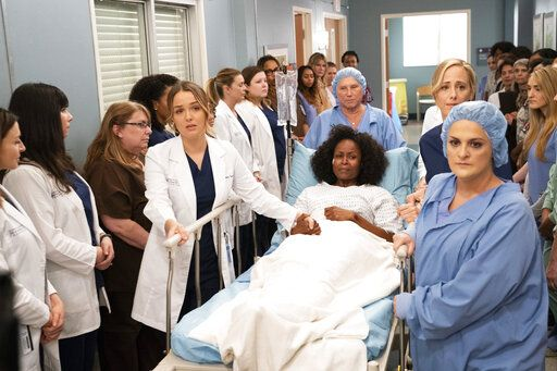 "This image released by ABC shows the cast of ""Grey's Anatomy"" in a scene from the episode ""Silent All These Years,"" where female doctors and nurses of Grey Sloan Memorial Hospital lined a hallway to both protect and support a rape victim, who had said every man she saw reminded her of her rapist. After it aired, it led to a 43% increase in calls to the National Sexual Assault Hotline. (Mitch Haaseth/ABC via AP)"