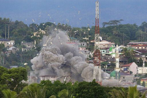 FILE - In this June 9, 2017, file photo, debris flies in the air as Philippine Air Force fighter jets bomb suspected locations of Muslim militants as fighting continues in Marawi city, southern Philippines. Philippine President Rodrigo Duterte decided to end martial law in the southern Philippines after more than two years after government forces weakened Islamic militant groups considerably with the capture and killing of their leaders, his spokesman said Tuesday, Dec. 10, 2019.