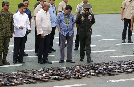 FILE - In this Dec. 13, 2018, file photo, Philippine President Rodrigo Duterte, center, looks at hundreds of guns and weapons confiscated during a pro-Islamic State group siege in Marawi, southern Philippines, at the Philippine Army Headquarters in Manila, Philippines. Duterte decided to end martial law in the southern Philippines after more than two years after government forces weakened Islamic militant groups considerably with the capture and killing of their leaders, his spokesman said Tuesday, Dec. 10, 2019.