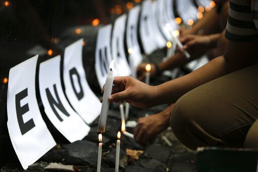 FILE - In this May 23, 2018, file photo, student protesters light candles to call on the government to end martial law in Mindanao province as they mark the anniversary of the siege by Islamic State group-aligned militants of Marawi city in southern Philippines, in Manila, Philippines. Philippine President Rodrigo Duterte decided to end martial law in the southern Philippines after more than two years after government forces weakened Islamic militant groups considerably with the capture and killing of their leaders, his spokesman said Tuesday, Dec. 10, 2019.
