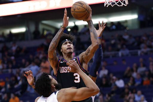 Phoenix Suns forward Kelly Oubre Jr. (3) shoots over Minnesota Timberwolves center Karl-Anthony Towns during the second half of an NBA basketball game, Monday, Dec. 9, 2019, in Phoenix.