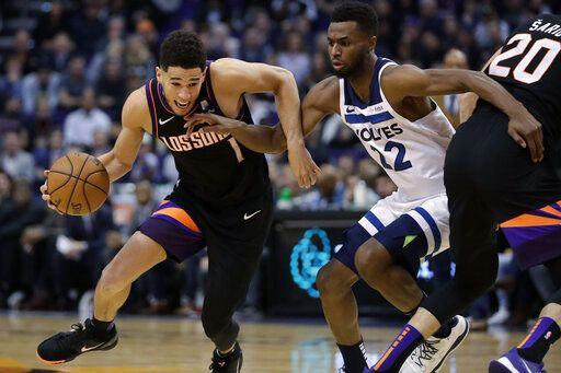 Phoenix Suns guard Devin Booker (1) drives around Minnesota Timberwolves forward Andrew Wiggins (22) during the second half of an NBA basketball game, Monday, Dec. 9, 2019, in Phoenix.