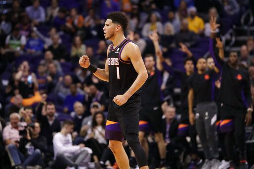 Phoenix Suns guard Devin Booker pumps his first after a basket during the second half of an NBA basketball game against the Minnesota Timberwolves, Monday, Dec. 9, 2019, in Phoenix.