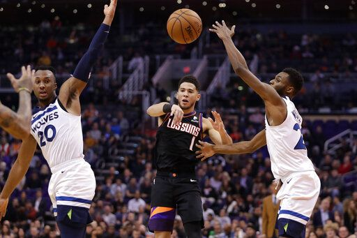 Phoenix Suns guard Devin Booker (1) passes between Minnesota Timberwolves guard Josh Okogie (20) and forward Andrew Wiggins during the second half of an NBA basketball game, Monday, Dec. 9, 2019, in Phoenix.