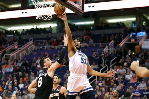 Minnesota Timberwolves center Karl-Anthony Towns (32) shoots over Phoenix Suns forward Frank Kaminsky (8) during the first half of an NBA basketball game, Monday, Dec. 9, 2019, in Phoenix.