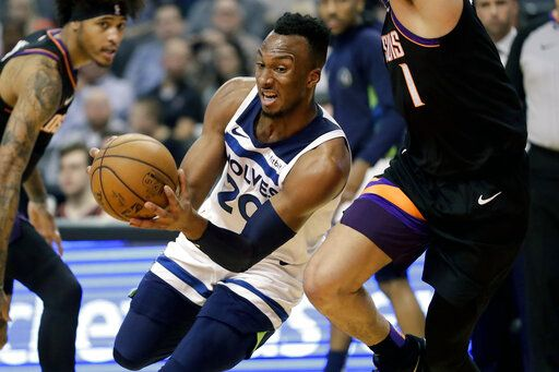 Minnesota Timberwolves guard Josh Okogie (20) drives past Phoenix Suns guard Devin Booker during the first half of an NBA basketball game, Monday, Dec. 9, 2019, in Phoenix.