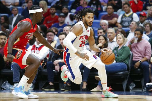Detroit Pistons guard Derrick Rose (25) drives by New Orleans Pelicans guard Jrue Holiday (11) in the first half of an NBA basketball game in New Orleans, Monday, Dec. 9, 2019.