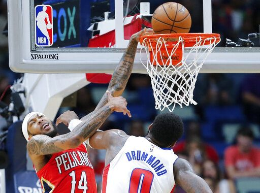 New Orleans Pelicans forward Brandon Ingram (14) draws a foul while dunking over Detroit Pistons center Andre Drummond (0) in the first half of an NBA basketball game in New Orleans, Monday, Dec. 9, 2019.