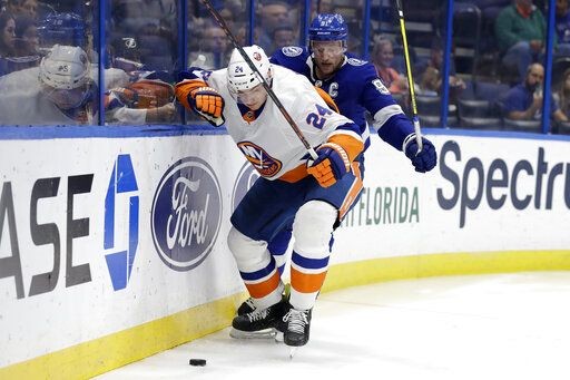 New York Islanders defenseman Scott Mayfield (24) moves the puck in front of Tampa Bay Lightning center Steven Stamkos (91) during the second period of an NHL hockey game Monday, Dec. 9, 2019, in Tampa, Fla.