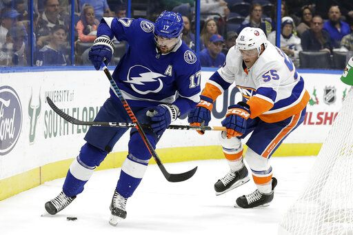 Tampa Bay Lightning left wing Alex Killorn (17) kicks the puck away from New York Islanders defenseman Johnny Boychuk (55) during the second period of an NHL hockey game Monday, Dec. 9, 2019, in Tampa, Fla.