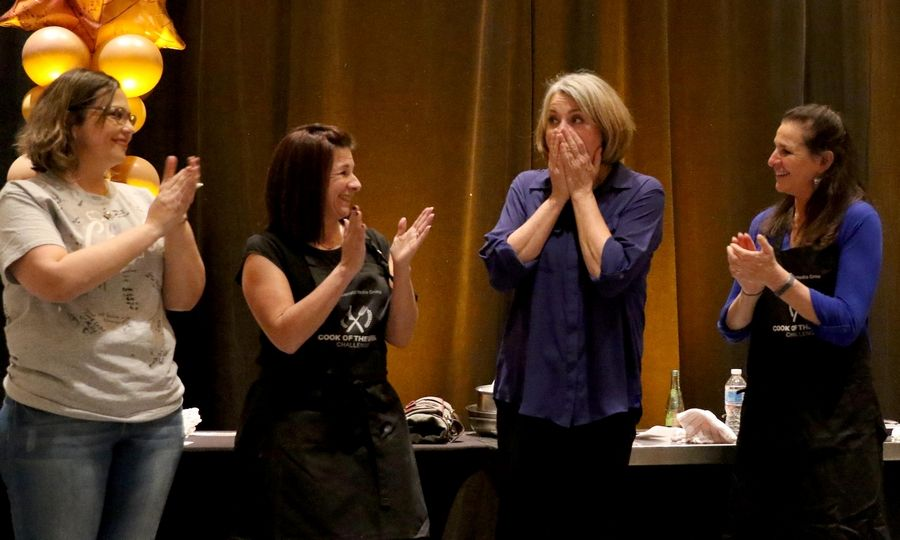 Leslie Meredith, second from right, reacts as her name is called making her winner of the Daily Herald Cook of the Week Challenge. With her, from left, are finale winner at the Westin in Itasca on Monday evening. From left are finalists Lulu Chapa of Volo, Lisa Eberhahn of Mount Prospect, and Ann Wayne of Barrington.