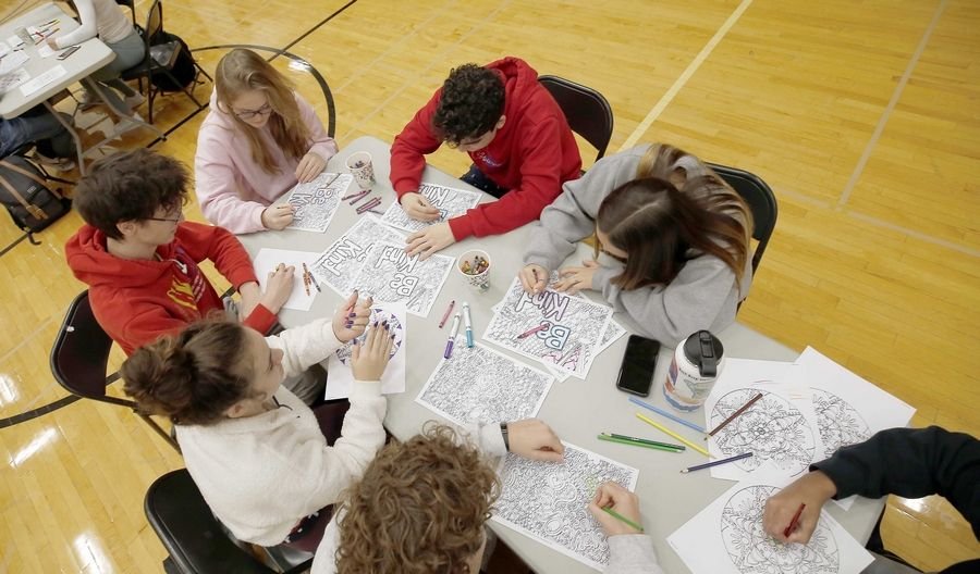 "Students take some time out to color in the gymnasium Wednesday at Metea Valley High School in Aurora, as physical education teachers host ""Stop Everything and Chill"" day before finals start next week. The chill activities such as coloring and yoga promoted student mental health at a high-pressure time of year."