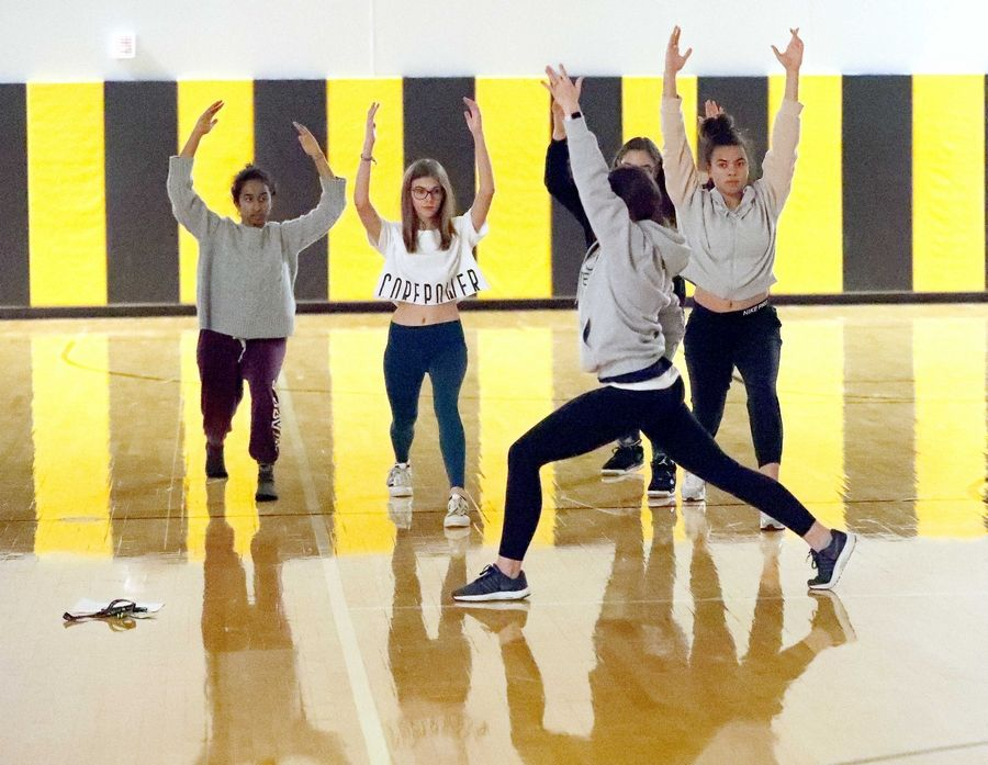 "Meghan Flannagan leads a yoga session Wednesday as physical education classes at Metea Valley High School in Aurora host a ""Stop Everything and Chill"" day before finals start next week. The activities in gym classes offered a way to promote student mental health by encouraging relaxation."