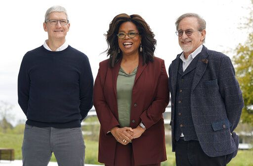 FILE - This March 25, 2019 file photo shows Apple CEO Tim Cook, from left, Oprah Winfrey and Steven Spielberg outside the Steve Jobs Theater during an event to announce new Apple products in Cupertino, Calif. Apple TV Plus launched Nov. 1 with Winfrey and Spielberg among its first wave of producers, and was quickly followed by Disney Plus.