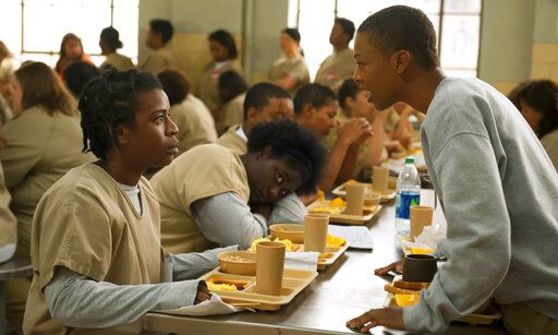 "FILE - In this file image released by Netflix, Uzo Aduba, left, and Samira Wiley appear in a scene from ""Orange is the New Black.""  It took less than a decade for leader Netflix to skyrocket from about 12 million U.S. subscribers at the decade's start to 60 million this year and 158 million worldwide.  (Jojo Whilden/Netflix via AP, File)"